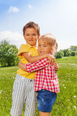 Boy and girl hugging in green field — Stock Photo
