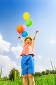 Happy girl with balloons wearing flower circlet — Stockfoto