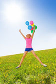 Jumping positive girl with balloons in summer — Stock Photo