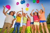Kids stand in half round with arms up to balloons — Stock Photo