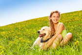 Cute happy girl cuddling dog in summer — Stock Photo