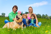Happy family sitting on green grass with dog — Foto Stock