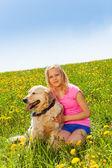 Smiling girl cuddling dog sitting on the grass — Stock Photo