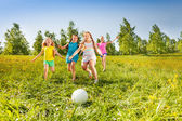 Group of children running to the ball in meadow — Stock Photo