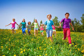 Running children holding hands in green meadow — Stock Photo