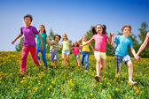 Happy kids run and hold hands in green meadow — Stock Photo