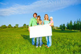 Happy family holds white square paper format — Stockfoto