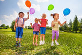 Small kids with four balloons in green meadow — Stock Photo