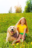 Happy girl and dog sitting on the grass — Stock Photo