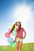 Beautiful girl with balloons in sunny day — Stock Photo