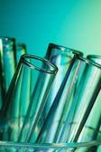Glass test tubes lighted with blue green light — Stock Photo