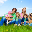 Smiling family sitting on green grass with dog — Stock Photo #48560071