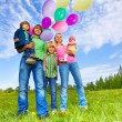 Happy family stands with balloons in park — Stock Photo #48560073