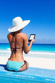 Beautiful woman from back reads kindle with hat — Stock Photo
