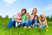 Smiling family sitting on green grass with dog — ストック写真