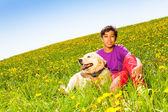 Boy hugging dog sitting on green grass in summer — Stock Photo