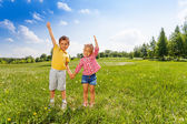 Boy and girl hold hands with second hand up — Stock Photo