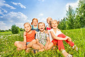 Children sitting on a grass — Stock Photo