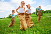 Kids jumping with sacks — Stock Photo