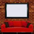 Red sofa with picture frame over brick wall — Stock Photo