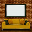 Sofa with picture frame over brick wall — Stock Photo
