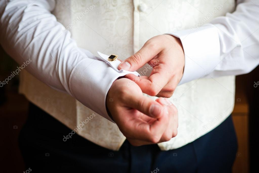 A man putting on his cuff links — Stock Photo #16235397