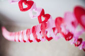 Red textured hearts hanging — Stock Photo