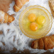 The broken eggs and baking on the wooden board poured by a flour — Stock Photo