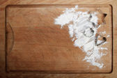 The form for cookies on the wooden board poured by a flour — Stock Photo