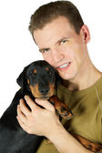 The man in a green t-shirt embraces a puppy of a Jagdterrier, a — Stock Photo