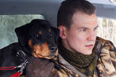 The man with the German hunting terrier sit in the machine. — Stock Photo