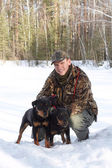 El hombre tiene una pista de dos perros de caza jagdterriers en la — Foto de Stock