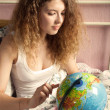 The girl with long hair looks for something on the globe — Stock Photo