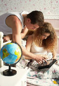 The married couple looks for something on the tablet computer in — Stock Photo
