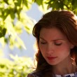 Stock Photo: The beautiful girl in a foliage border thoughtfully looks down