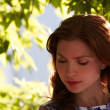 The beautiful girl in a foliage border thoughtfully looks down — Stock Photo