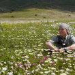 The man sits in the middle of a meadow in the mountains of Armen — ストック写真