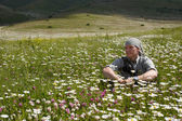 The man sits in the middle of a meadow in the mountains of Armen — Stock Photo