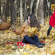 Mother with two children sits on an edge of the autumn wood, col — Stock Photo