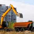 Excavator loads the ground in a truck on a background of houses — Stock Photo