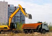 Excavador de cargas de la tierra en un camión en un fondo de casas — Foto de Stock