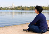 Woman sitting on the sand by the river — Stock Photo