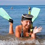 flicka med fenor och mask ligger i havet — Stockfoto