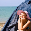 Girl calls by phone, sitting in tent on beach — Stock Photo #20226373