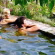 Stock Photo: Two women are swimming in the pool at their summer cottage