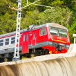 Railways train on background of green mountain slopes — Stock Photo
