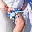 Lacy garter on the leg of bride — Stock Photo