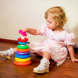 Stock Photo: Little girl collects pyramid on laminate floor