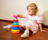 Little girl collects pyramid on laminate floor — Stock Photo