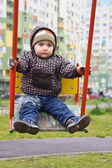 Child swinging on a swing in the yard — Foto Stock